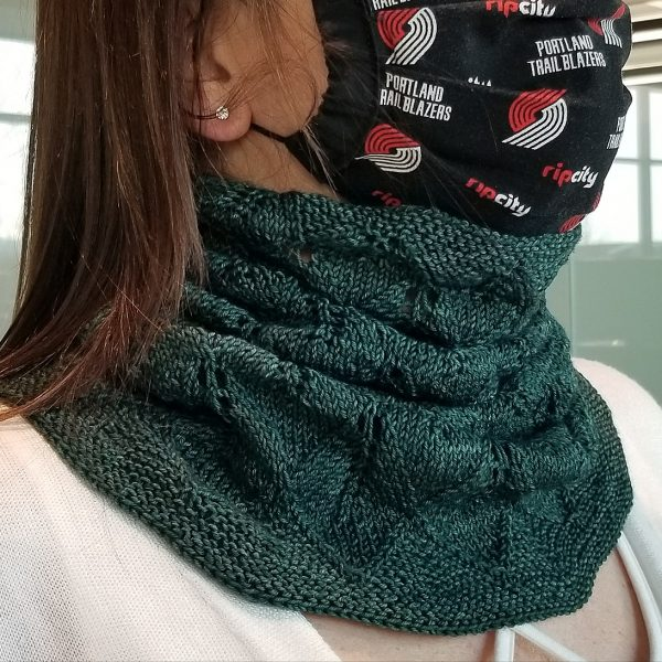 A model wearing a cowl in dark green yarn with diamond shaped lace leaves and a wide garter stitch border