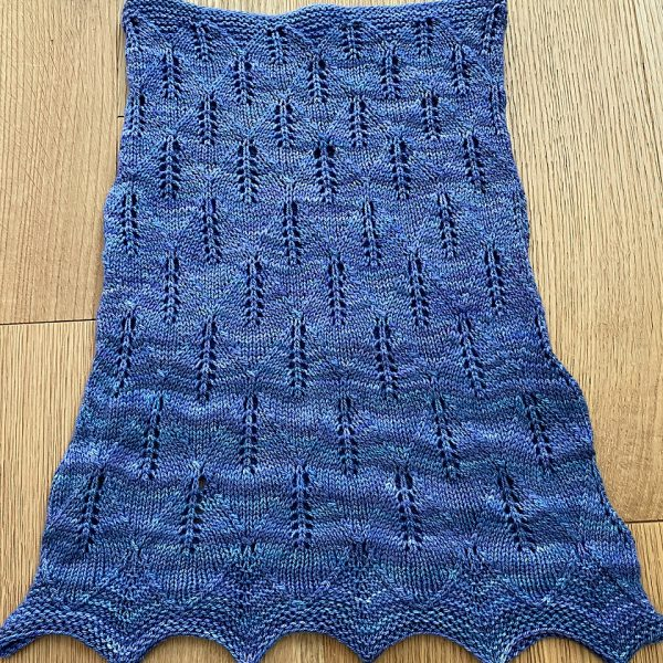 A blue coloured cowl with diamond shaped lace leaves and wide garter stitch borders laid flat
