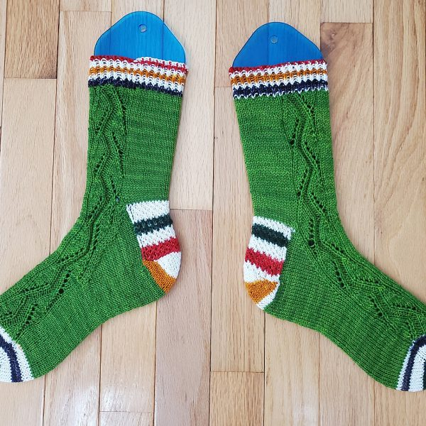 A pair of socks handknit in green yarn with contrast heels and toes laid flat to show the zigzag lace pattern up the outside of each foot and leg