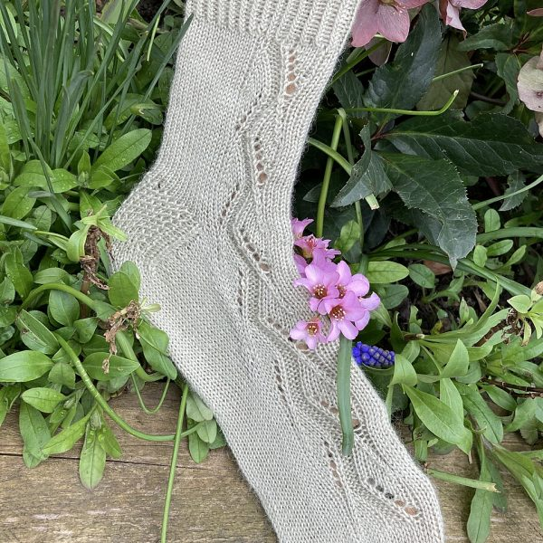 A sock handknit in pale green yarn on a sock blocker to show the zigzag lace pattern up the outside of the foot and leg