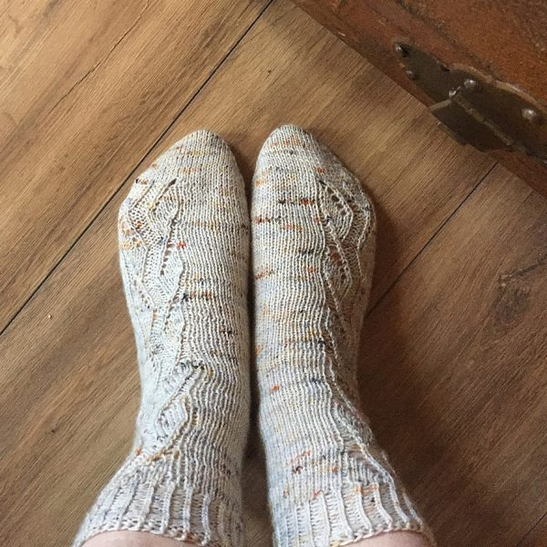 A pair of socks handknit in white speckled yarn showing the zigzag lace pattern up the outside of each foot and leg,