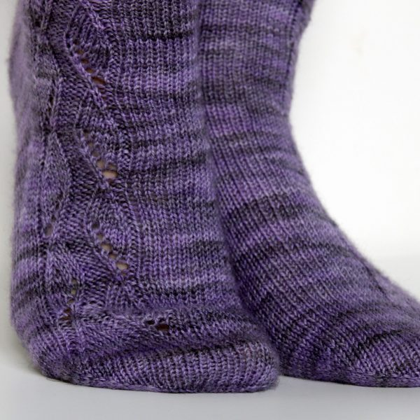 A close up on the toes of a purple pair of socks with a zigzagging lace pattern up the outside of each foot