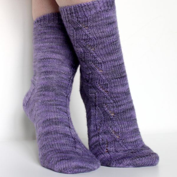 A pair of socks handknit in purple yarn showing the zigzag lace pattern up the outside of one foot and leg, and showing the gusset and textured heel pattern on the other foot