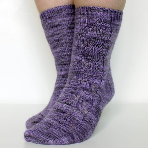 A pair of socks handknit in purple yarn showing the zigzag lace pattern up the outside of one foot and leg,