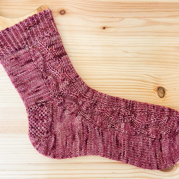 A sock handknit in pink yarn laid flat to show the zigzag lace pattern up the outside of the foot and leg