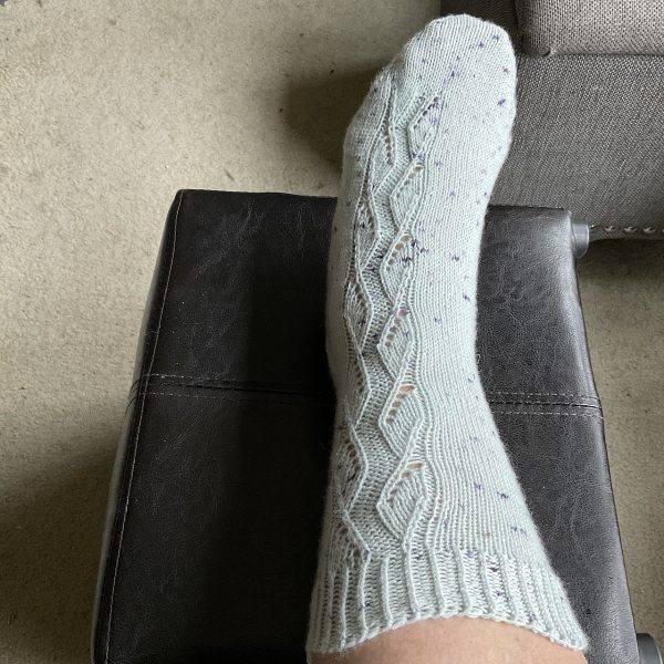 A sock handknit in white speckled yarn showing the zigzag lace pattern up the outside of the foot and leg