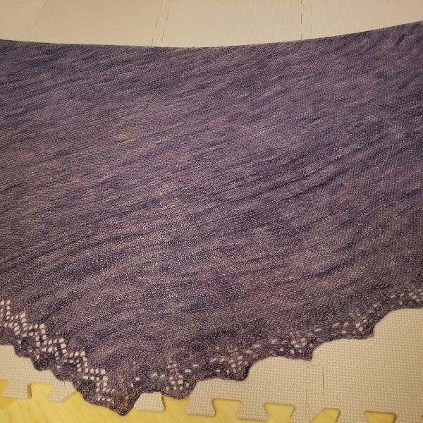 A purple shawl with a diamond edge and a rippled border folded on a blocking mat