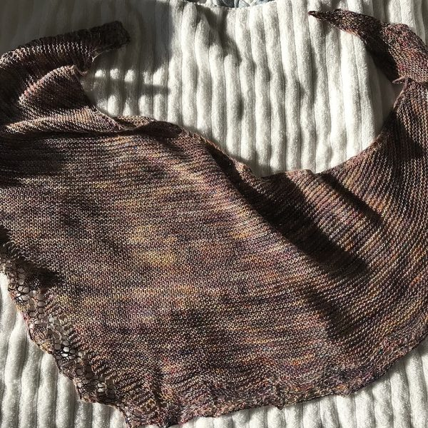 A brown shawl with a diamond edge and a rippled border laid on a blanket