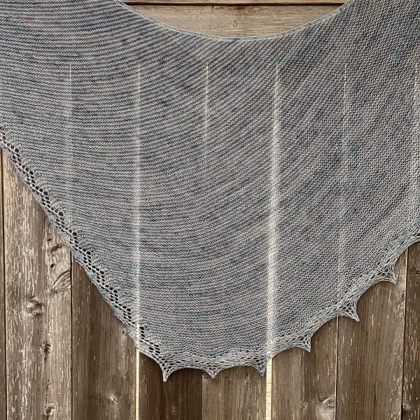 A silvery grey shawl with a diamond edge and a rippled border over a fence