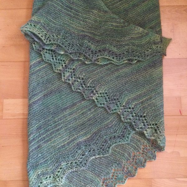 A green variegated shawl with a diamond edge and a rippled border folded on a wooden background