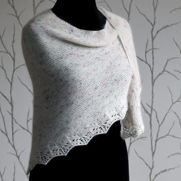 A white speckled shawl with a rippling lace pattern along the edge modelled on a mannequin