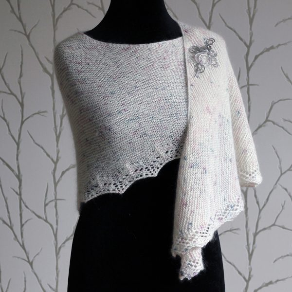 A white speckled shawl with a rippling lace pattern along the edge modelled on a mannequin with a silver shawl pin