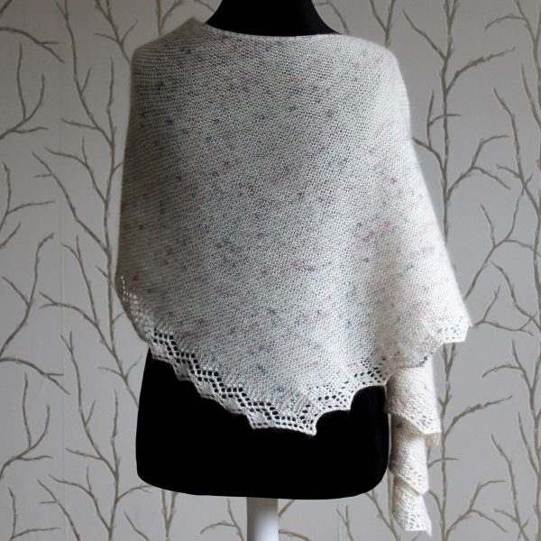 A white speckled shawl with a diamond lace pattern along one edge and a rippled border on the other draped over a mannequin