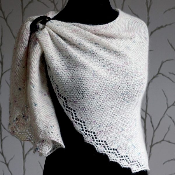 A white speckled shawl with a diamond lace pattern along the edge modelled on a mannequin with a shawl cuff