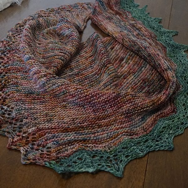 A variegated shawl with a diamond edge and a contrast rippled border on a wooden background