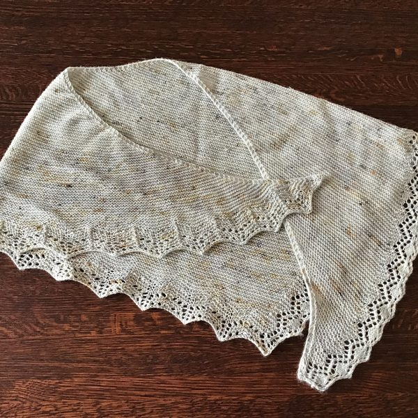 A speckled cream shawl with a diamond edge and a rippled border folded on a wooden background