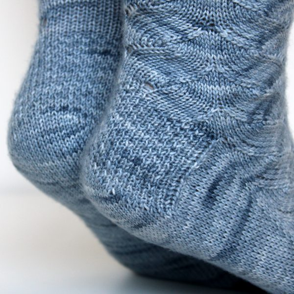 A modelled pair of socks knit in light blue grey yarn showing the textured heel pattern