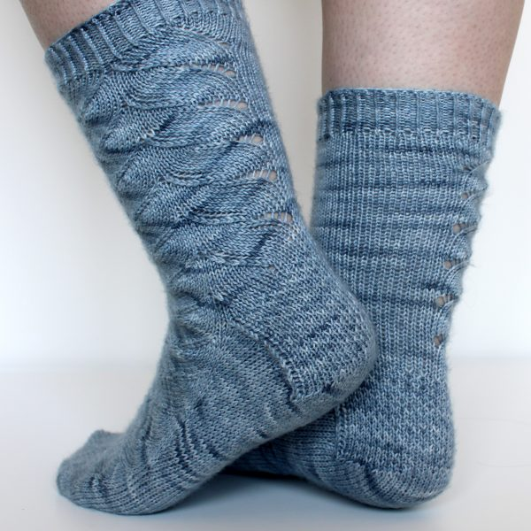 A modelled pair of socks knit in light blue grey yarn with a lace pattern swirling to the outside of the foot and into the middle of the leg and showing the textured heel pattern