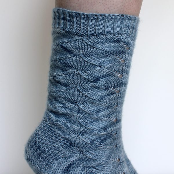 A modelled pair of socks knit in light blue grey yarn with a lace pattern swirling to the outside of the foot and into the middle of the leg