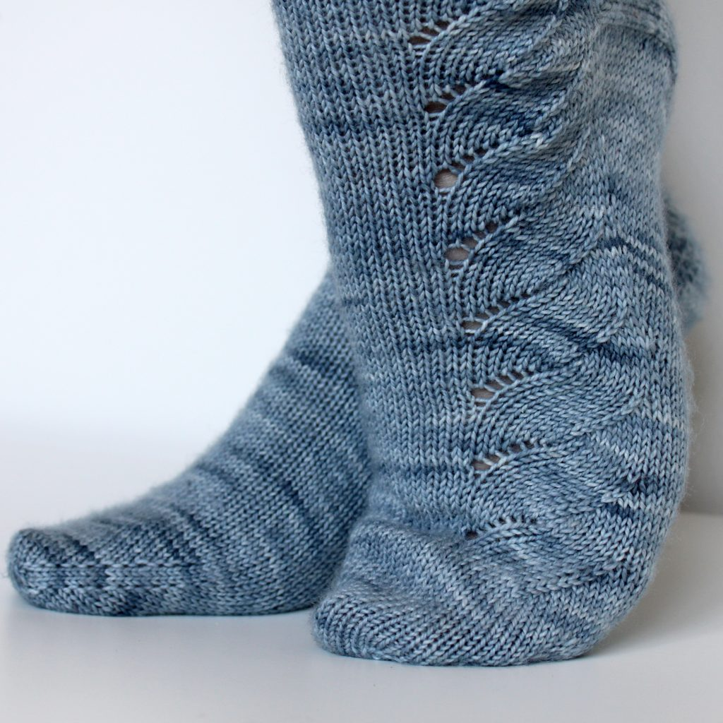 A modelled pair of socks knit in light blue grey yarn with a lace pattern swirling to the outside of the foot